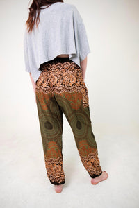 Rear-view mandala elephant pants in olive green with model and white background-fullsize image
