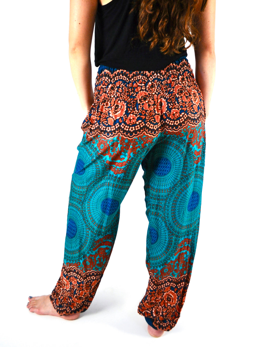 Rear-view mandala elephant pants in orange & teal with model and white background-fullsize image