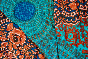 Close-up on mandala elephant pants pattern in orange & teal
