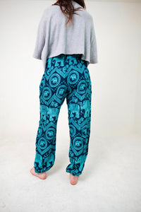 Rear-view tribal elephant pants in teal with model and white background-full-size image