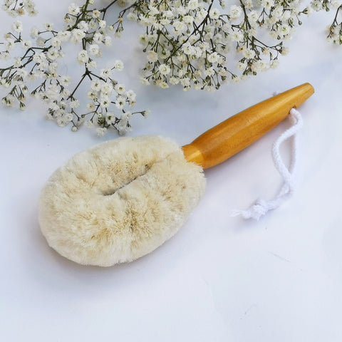 facial dry brush with white flowers in background