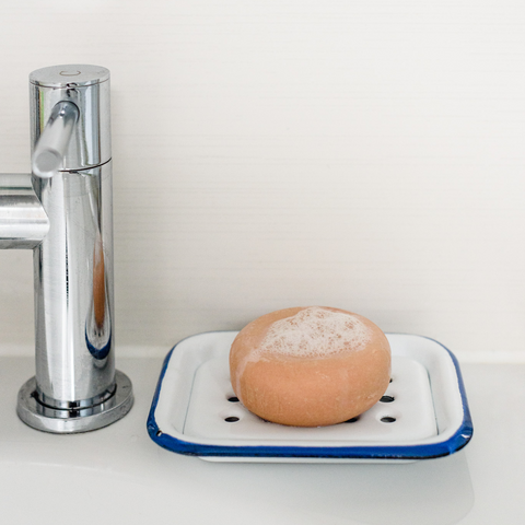 silver tap with shampoo bar or white and blue metal soap dish
