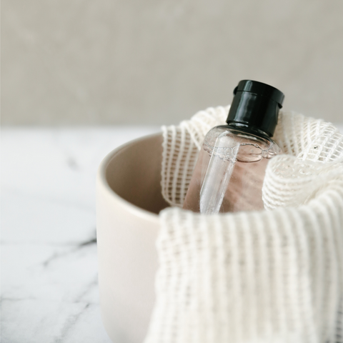 beauty product in clear bottle inside soft pink basket with white fabric