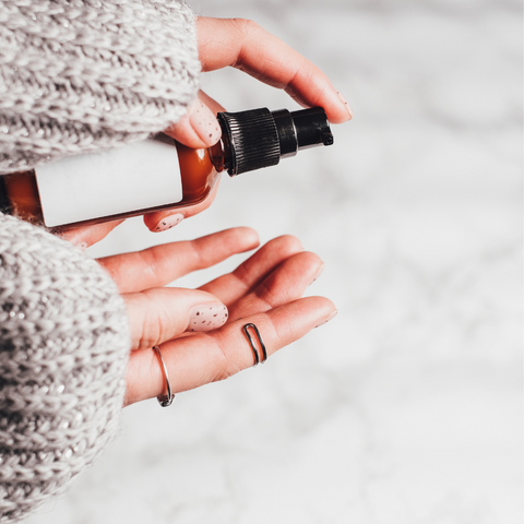 woman pumping bottle of skincare into her hand with wooly jumper