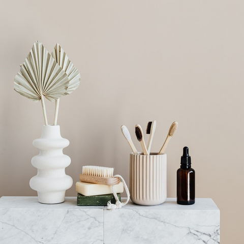 range of beauty products on a marble shelf including soap, bamboo toothbrush and oil bottle