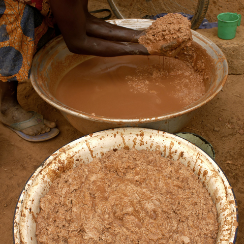 2 silver bowls on mud floor with shea butter being processed inside