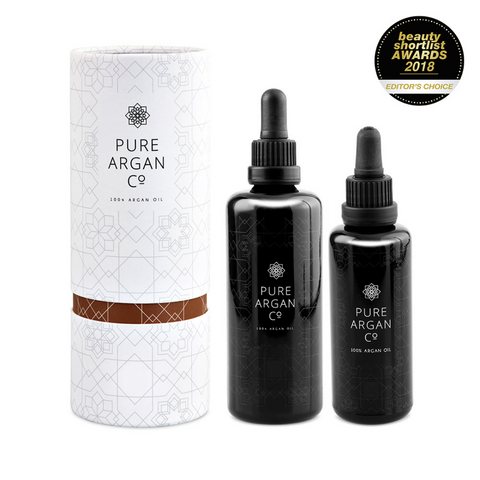 3 bottles of organic argan oil, one in white tube packaging with award logo