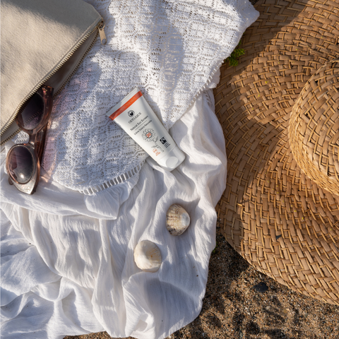 organic sunscreen on sandy beach with sunhat, sunglasses and coverup