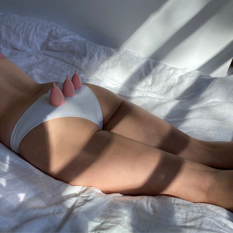 3 period cups resting on woman lying on her front in white pants