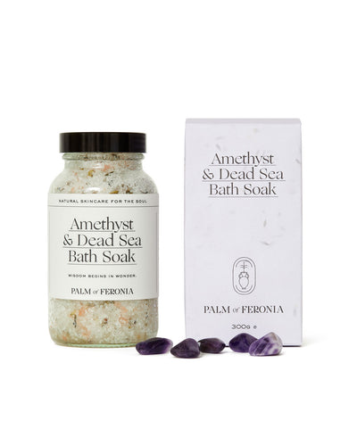 palm of feronia bath salts. clear jar of multi coloured bath salts with black lid on left and a white seeded paper box on the right with some amethyst stones in the foreground