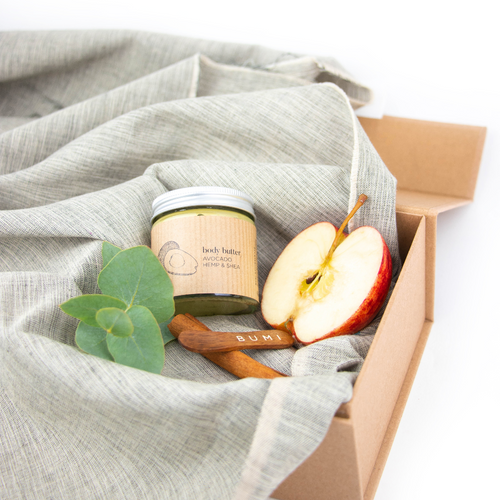 avocado body butter in clear glass jar with aluminium lid in brow gift box with grey fabric and some eucalyptus, apple and cinnamon