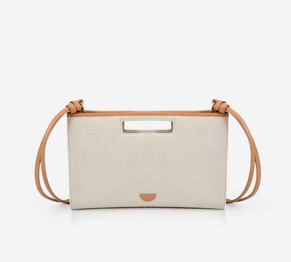 Lana bag in beige almond colour. Canvas leather handbag. Clutch it or sling it. Waterproof canvas, genuine leather detachable strap, inside lining, gold hardware, inside and back compartments.