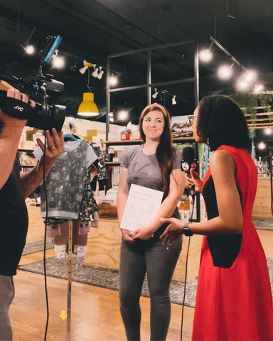 Two women on a news interview, standing inside a local store full of handmade goods in Spokane, Washington