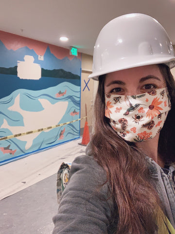 Woman in a hard hat and mask stands in front of a mural that is in progress. The mural is of a Washington State Ferry with the Olympic mountains in the background and orcas under in the water.