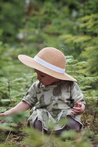A little girl sits in the grass with a morel dress on. She is picking some foliage with a pine tree in the background.