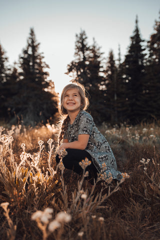 Little girl in a grey raccoon dress sits in a flowery field with trees behind her smiling at the sky.