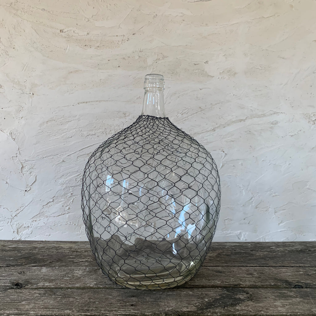 massive caged wire cellar bottle