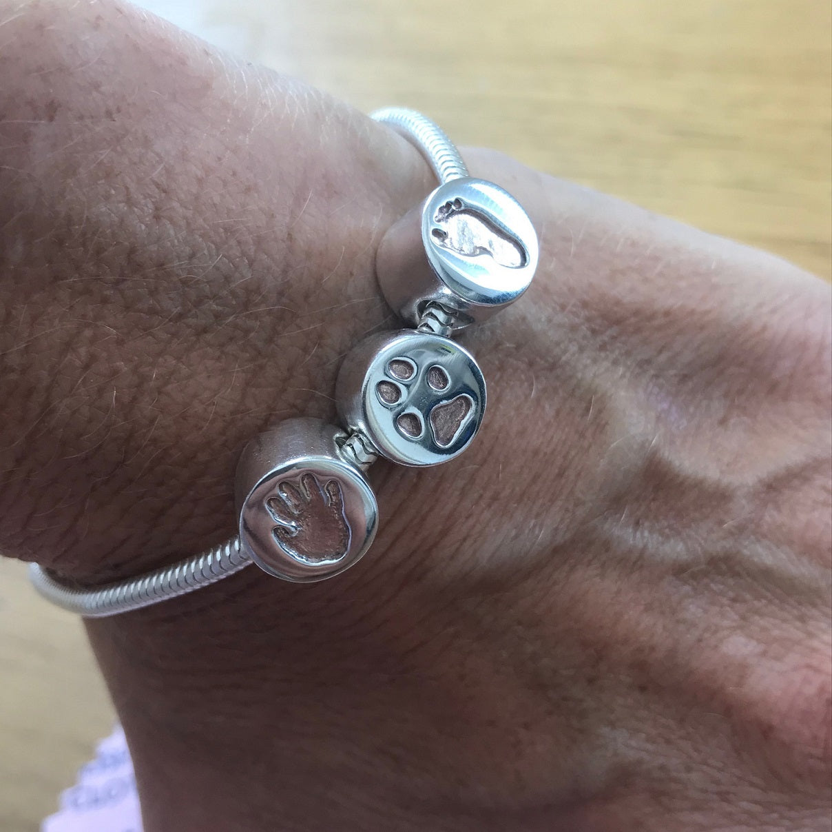 Lady wearing Pandora Style Bracelet Circle Charm Bead with Rose Gold. Sterling Silver Handprint Jewellery