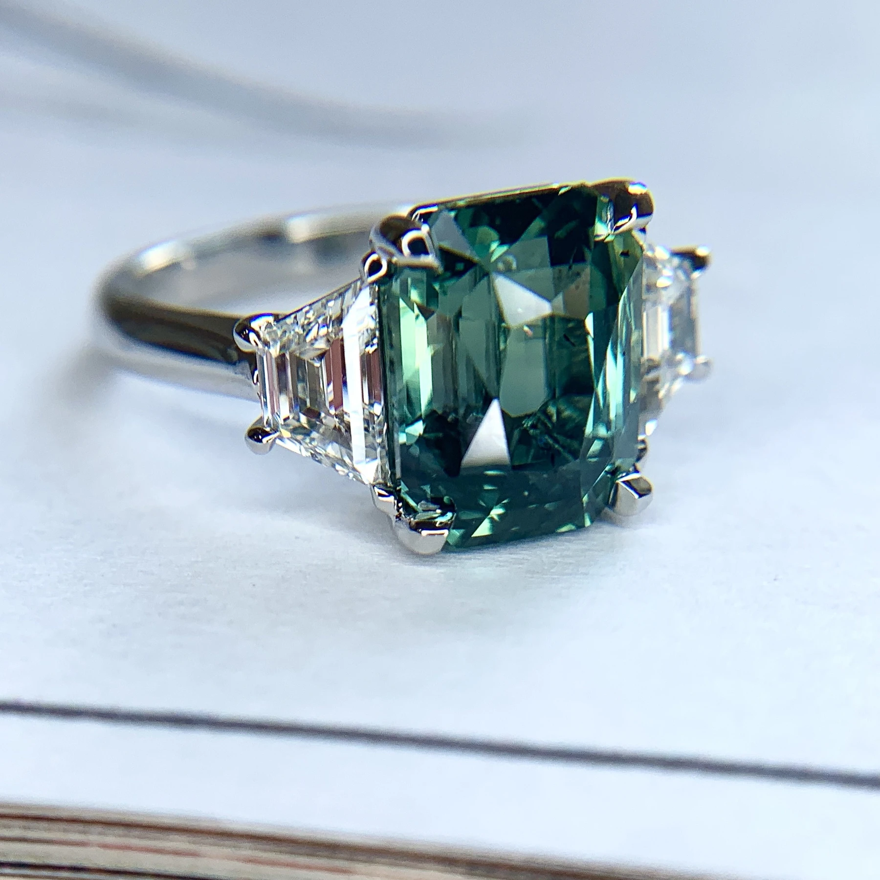 Green sapphire emerald cut engagement ring with diamond accents