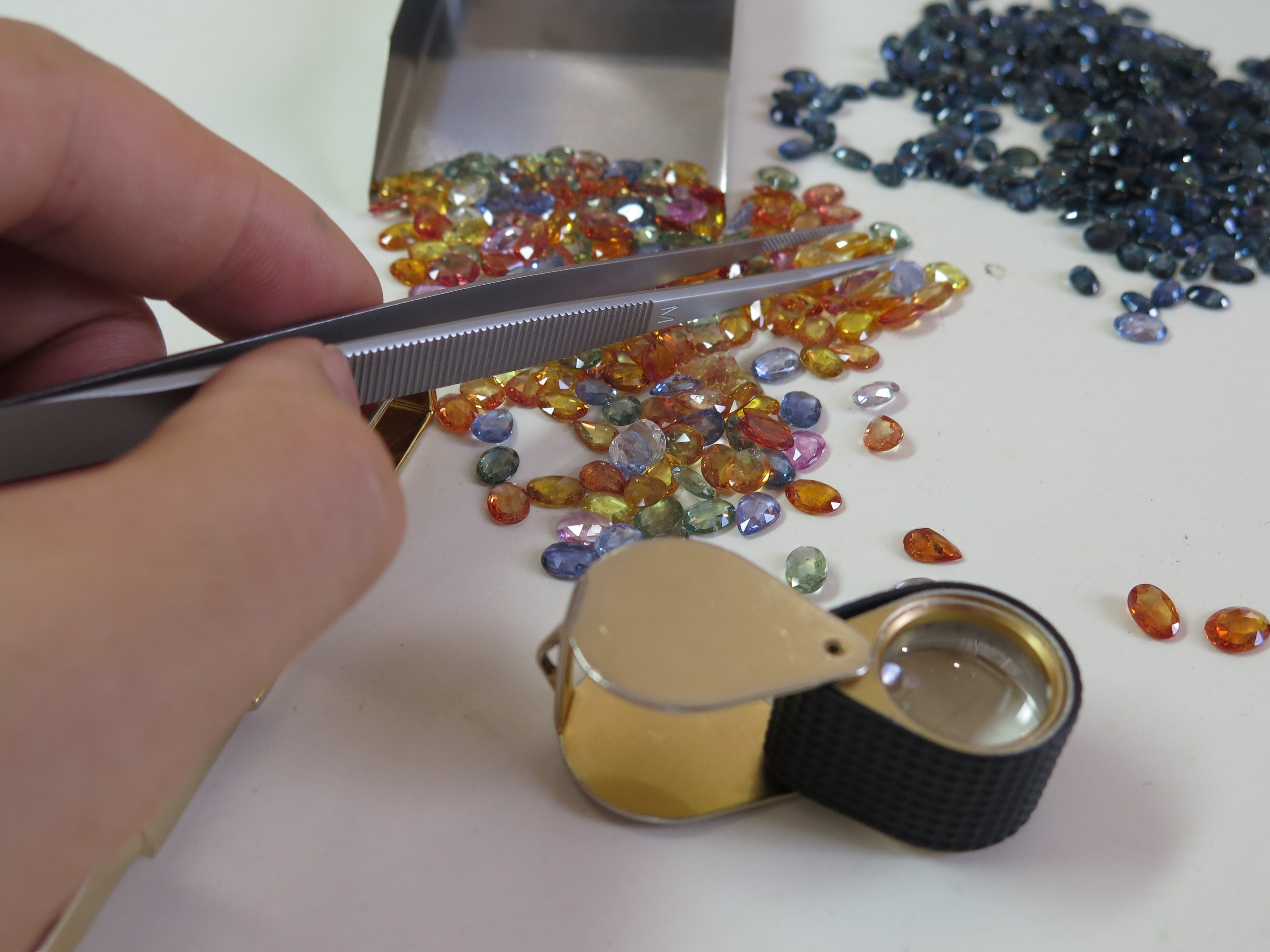 Sapphire gemstones with jewelry tweezers and loupe- Dana Walden Studio