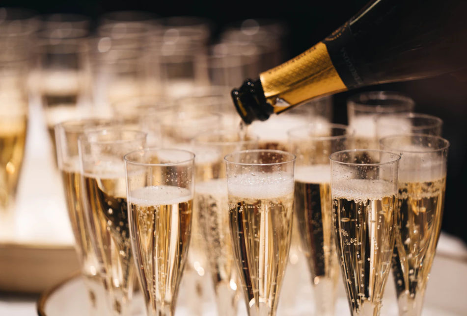 Champagne glasses being filled- Unsplash