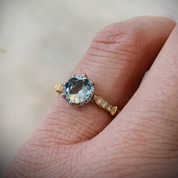 Unique aquamarine engagement ring in yellow gold with vintage inspired details & low profile - shown on hand - Aminta