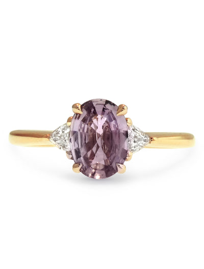 Mauve sapphire engagement ring flanked by trillion shaped diamonds in yellow gold, designed by dana walden bridal