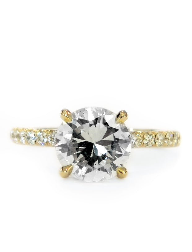 Diamond solitaire engagement ring in yellow gold with accent diamonds underneath stone and in band
