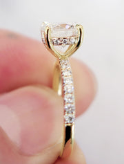 Delicate diamond engagement ring in yellow gold with accent diamonds underneath stone and in band from side