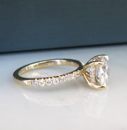 Diamond solitaire engagement ring in yellow gold with accent diamonds underneath stone and in band from side profile
