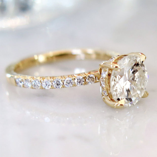Delicate diamond solitaire in yellow gold with accent diamonds underneath center stone and micro-pave