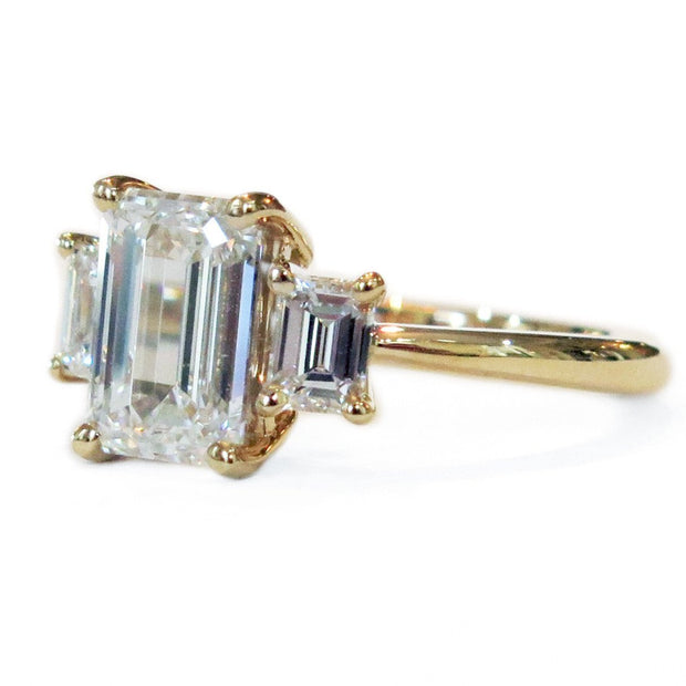 Delicate emerald cut three stone engagement ring in yellow gold custom made in nyc - emma