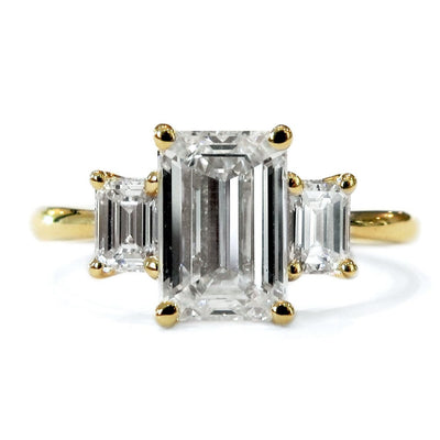 Classic 2 carat emerald cut three stone engagement ring in yellow gold with delicate band