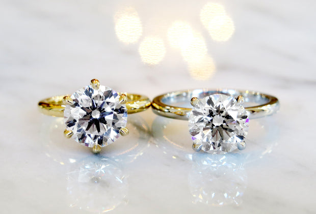 Custom diamond solitaires with delicate bands in yellow gold & platinum