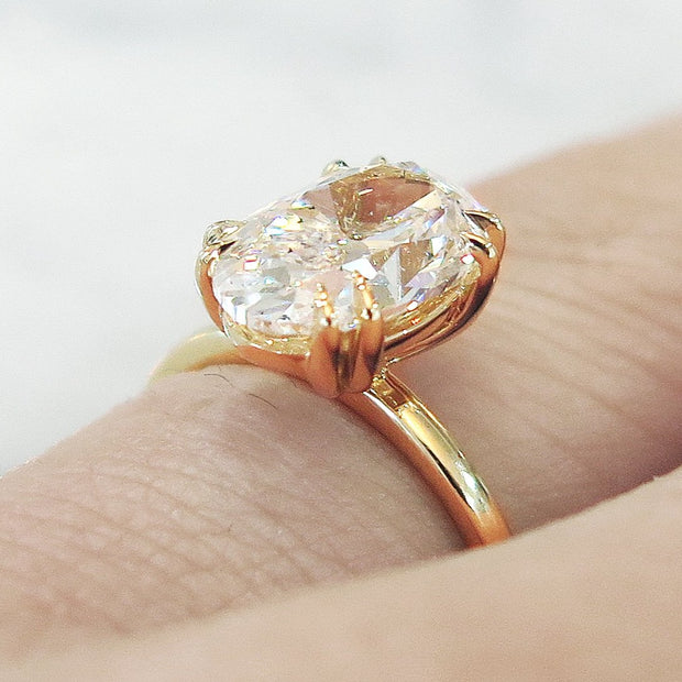 Oval diamond engagement ring, yellow gold solitaire, low profile & delicate, on hand, 2 carat diamond
