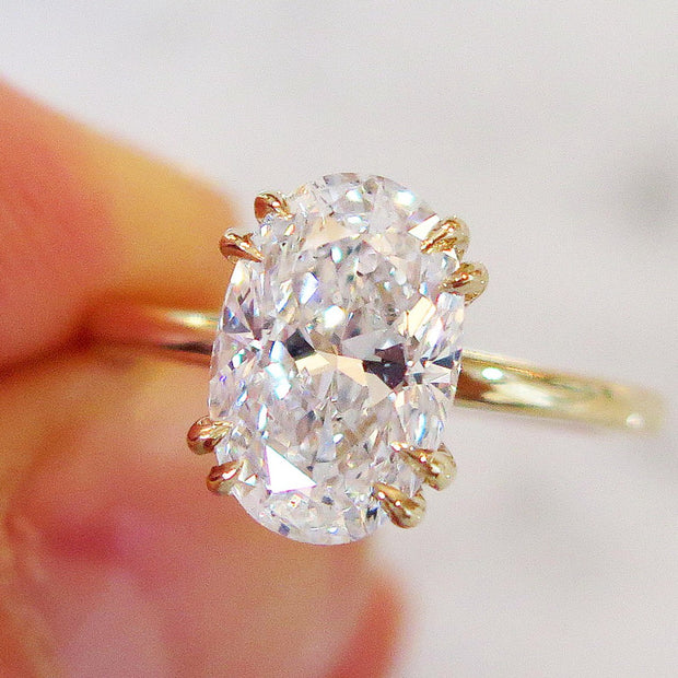 Oval diamond solitaire engagement ring, 2 carats, yellow gold setting, thin band, in hand