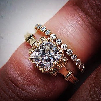 Unique cushion cut diamond engagement ring with wedding band in yellow gold on hand