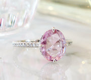 Large 2.25 carat peach sapphire engagement ring with delicate band and diamond accents