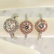 A trio of rose gold and platinum halo engagement rings