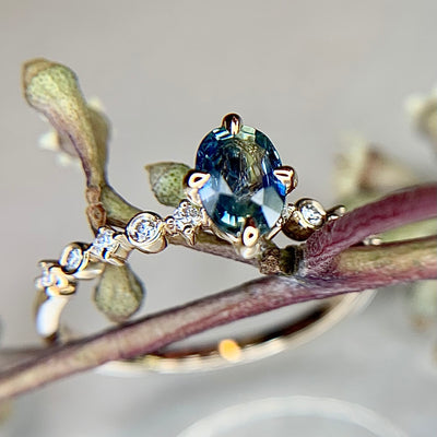 Blue green bicolor sapphire engagement ring with teal hues in yellow gold & diamond band by Dana Walden Bridal NYC