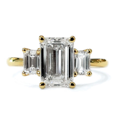 A large emerald-cut diamond flanked by two smaller emerald cut diamonds form a classic three-stone engagement ring design set in yellow gold. Dana Walden NYC.