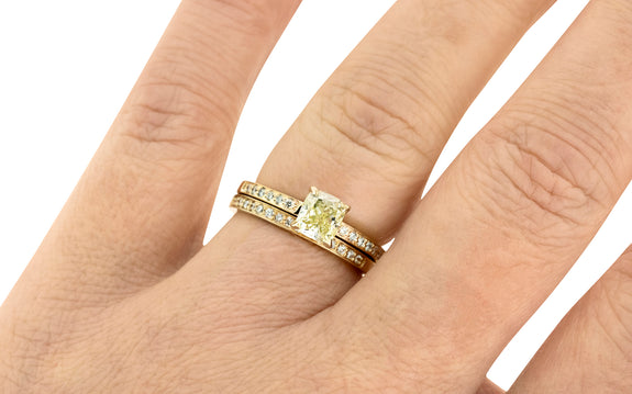 1.01 carat sparkling champagne diamond ring prong set in 14 karat yellow gold with six pave diamonds on each shoulder paired with 14 karat yellow gold band with 16 pave diamonds top view on finger
