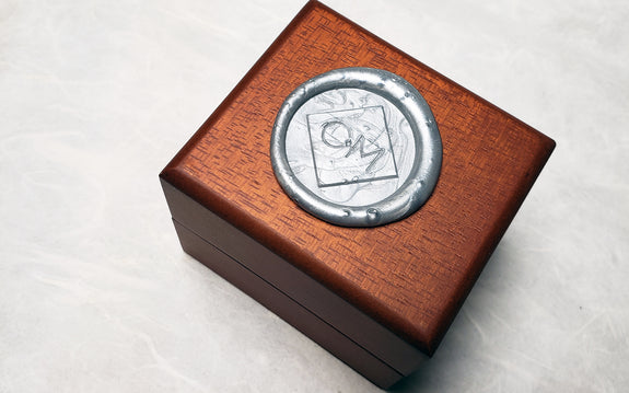 wooden Chinchar Maloney jewelry box with sealing wax logo on white background
