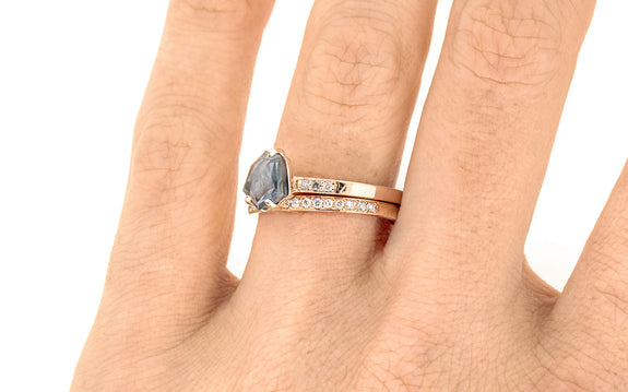 1.05 Carat Hand-Cut Violet/Blue Sapphire Ring on a hand with wedding band