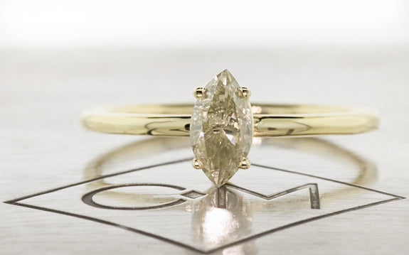 Pear shaped champagne diamond set in yellow gold ring front view on metal background with Chinchar Maloney logo