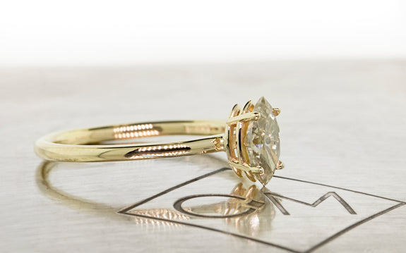 Pear shaped champagne diamond set in yellow gold ring side view on metal background with Chinchar Maloney logo