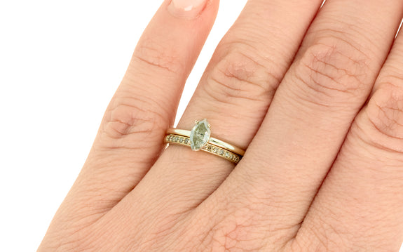 Pear shaped champagne diamond set in yellow gold ring on finger paired with diamond band