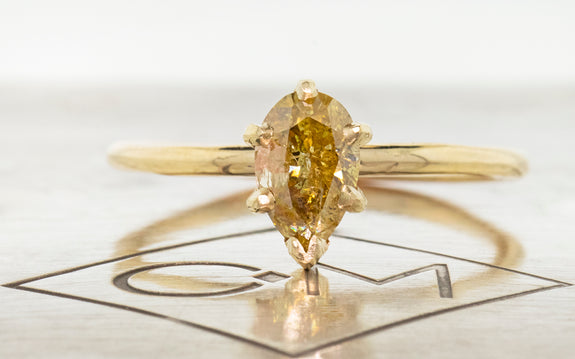 Pear shaped honey champagne diamond set in yellow gold front view with metal background and Chinchar Maloney logo