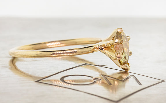 Pear shaped honey champagne diamond set in yellow gold side view with metal background and Chinchar Maloney logo