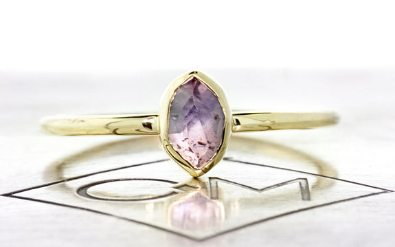 .77 carat hand cut purple sapphire in bezel setting in 14 karat yellow gold front view on Chinchar Maloney metal plate